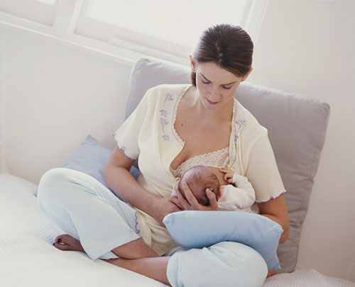 Woman sitting cross legged, supporting the head of a young baby with her hand and breastfeeding